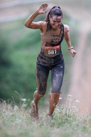 Ragazza che corre una gara di trail running nel fango